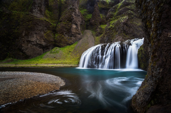 Waterfalls in Iceland surrounded by green moss by Sarah Marino