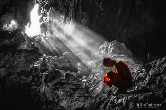 Travel photography example of a buddhist Monk in Tham Phu Kham cave by Clint Burkinshaw