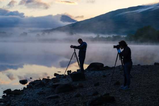 Two landscape photographers with tripods in the field by Ugo Cei