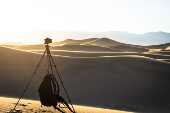 Camera backpack hanging from lightweight landscape photography tripod clip.